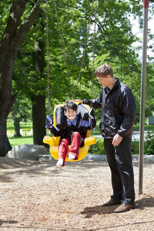 cerebral palsy: Father pushing disabled boy in special needs handicap swing. Child has cerebral palsy. Stock Photo