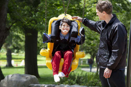 babysit: Father pushing disabled boy in special needs handicap swing. Child has cerebral palsy. Stock Photo