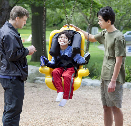 Disabled little boy swinging on special needs swing being pushed by family