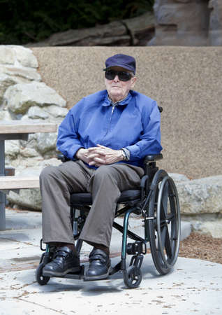 Elderly senior man in wheelchair sitting outside photo