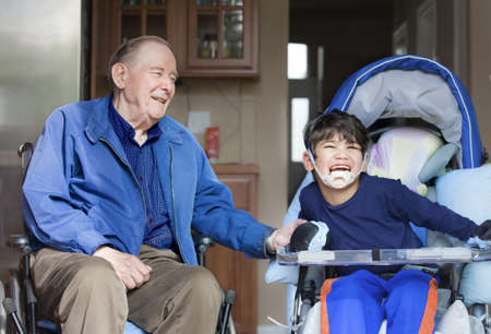 Elderly man in wheelchair laughing with disabled boy in kitchen photo