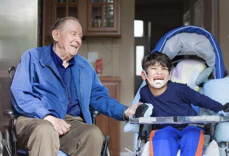 ni�o discapacitado: Hombre mayor en silla de ruedas riendo con ni�o discapacitado en la cocina