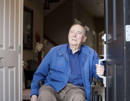 cadeira de rodas: Idoso de 90 anos de idade homem dentro cadeira de rodas em sua porta da frente, olhando para o c