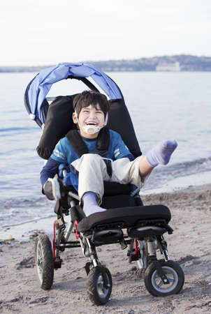 Happy disabled five year old boy in wheelchair on the beach photo