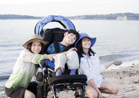 Zusters het verzorgen van gehandicapte broer in de rolstoel op het strand Stockfoto