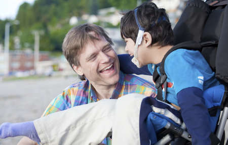 people with disabilities: Father and disabled five year old son laughing together on beach