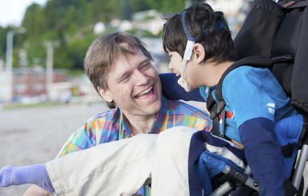 personas discapacitadas: Padre y discapacitados de cinco años hijo riendo juntos en la playa