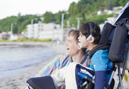 Vader en uitgeschakeld vijf jaar oude zoon op het strand en kijkt uit over het water Stockfoto