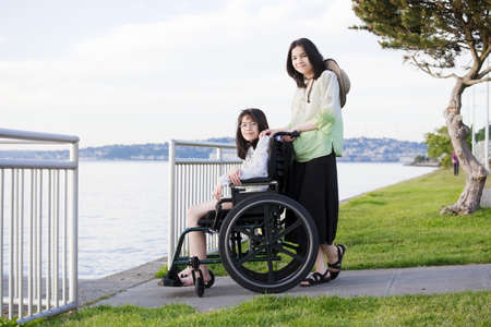 Young teen girl pushing sister in wheelchair outdoors by lake