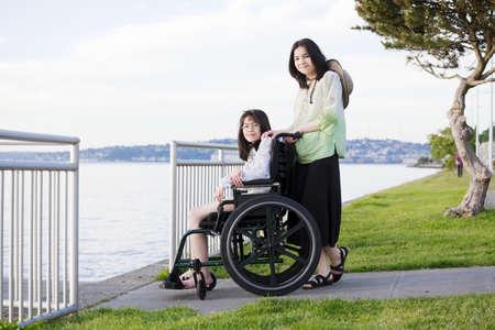 Niños ayudando: Niña adolescente empujando hermana en silla de ruedas al aire libre junto al lago