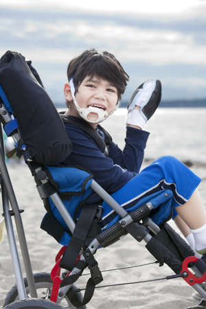 Happy disabled five year old boy in wheelchair on the beach, waving hello photo