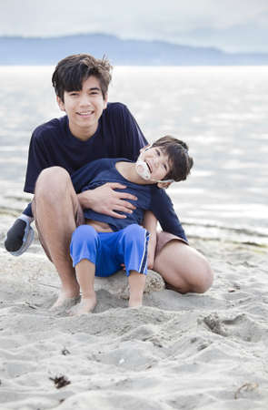 thai teen: Big brother holding disabled boy on beach, helping  him play in the sand