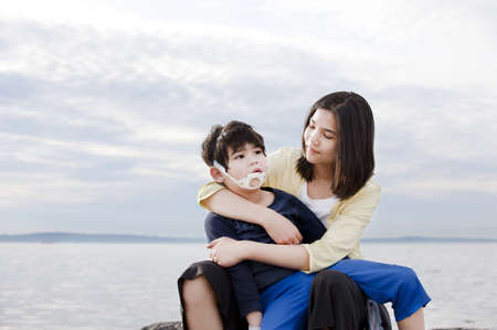 special needs: Teenage sister holding her disabled brother on the beach  Child has cerebral palsy