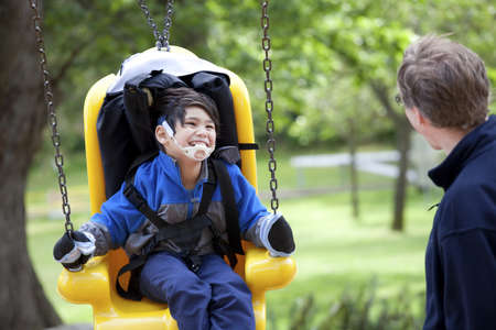 Father pushing disabled son  on yellow handicap swing photo