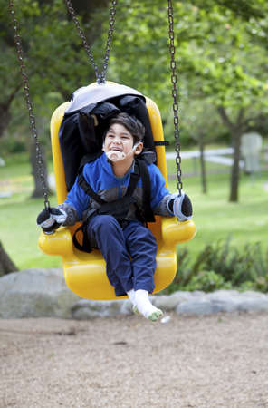 Disabled boy on yellow handicap swing photo