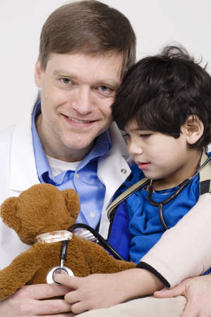Friendly doctor playing with five year old disabled patient during office visit by playing with teddy bear doll together photo