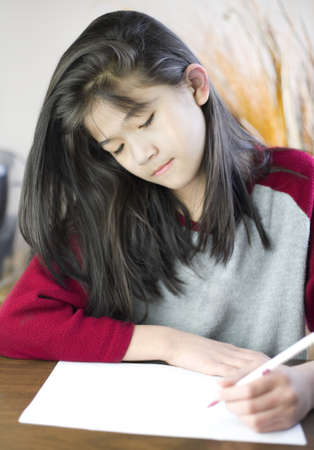 Ten year old biracial girl writing or drawing on paper Stock Photo - 15585034