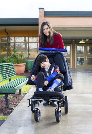 Teenage girl pushing her  little disabled brother in wheelchair leaving school