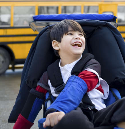 Disabled five year old boy in wheelchair, by schoolbus Stock Photo - 15584977