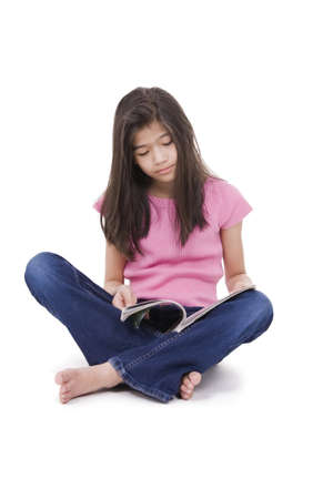 Ten year old Asian girl sitting on floor reading a magazine, isolated on white Фото со стока