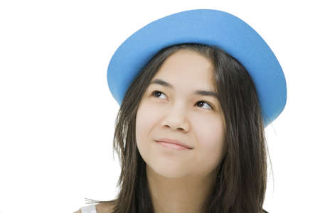 Beautiful young teen girl in blue hat, looking up with thoughtful expression.Isolated on white photo