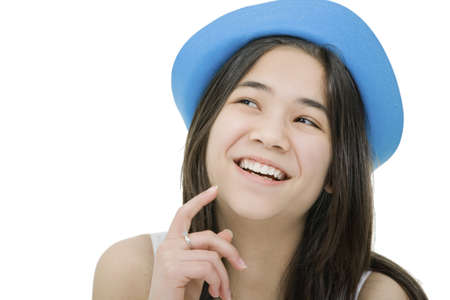 Beautiful young teen girl in blue hat, looking up with thoughtful expression, as if she has a fun idea or thought. Isolated on white photo