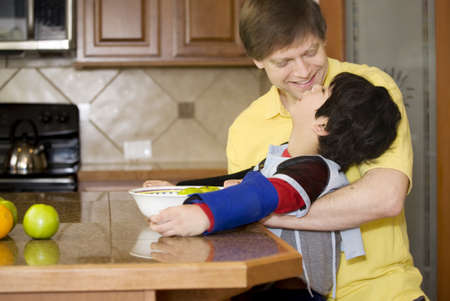 cerebral palsy: Father helping disabled son putting fruit into bowl in the kitchen. Son has cerebral palsy.