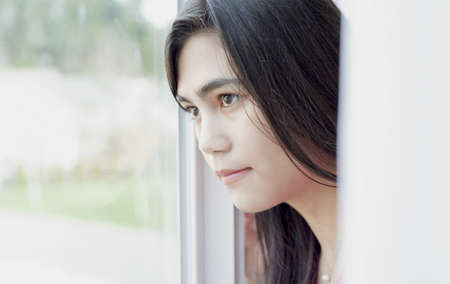 Side profile of teen girl or young woman looking out sunny window, sad or lonely expression