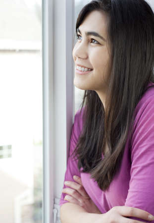 Side profile of teen girl or young woman looking out sunny window, happy or peaceful expression