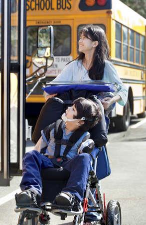 Diez años niña empujando poco chico discapacitado usar equipo de protección en silla de ruedas al lado del autobús escolar. El niño tiene parálisis cerebral. Foto de archivo - 15585140