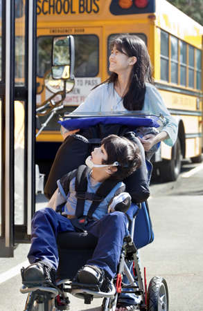Ten year old girl  pushing disabled little boy wearing protective gear  in wheelchair  next to school bus. Child has cerebral palsy. photo
