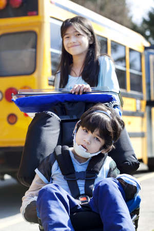 next year: Ten year old girl  pushing disabled little boy wearing protective gear  in wheelchair  next to school bus. Child has cerebral palsy.