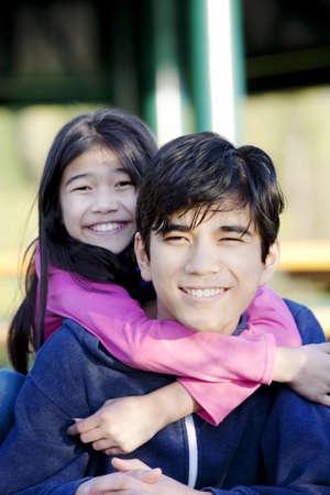 妹が兄の首の周りを抱き締める 写真素材