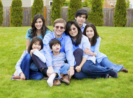 Grote multiraciale familie van zeven zitten samen op het gazon, gekleed in blauwe kleuren. Vijf jaar oude jongen voor is uitgeschakeld met een hersenverlamming.