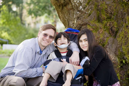 cerebral palsy: Happy disabled boy with cerebral palsy  in wheelchair surrounded by father and older sister, laughing Stock Photo