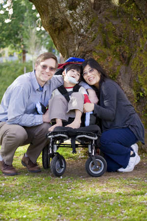 Happy disabled child in wheelchair surrounded by parents, outdoors. Cerebral palsy.