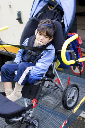 challenged: Disabled little boy on school bus wheelchair lift Stock Photo