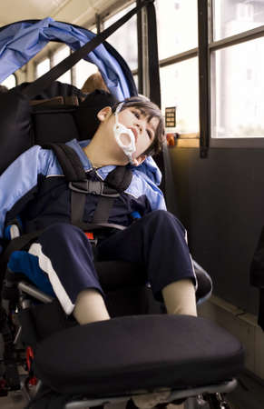 Disabled little boy sitting in wheelchair on school bus