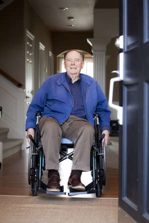 Elderly 90 yr old man in wheelchair at his front door photo