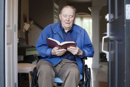 Elderly 90 yr old man in wheelchair at his front door, reading a Bible photo