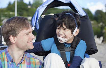 Vader en uitgeschakeld vijf jaar oude zoon samen lachen op het strand Stockfoto