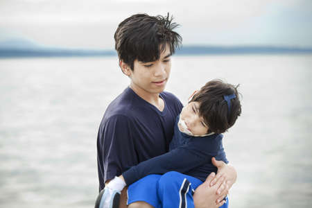 Big brother carrying disabled boy on beach by water. Child has cerebral palsy photo