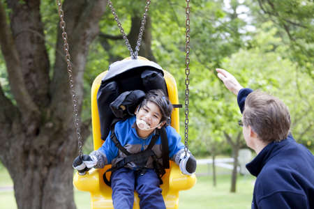 Father pushing disabled son  on yellow handicap swing Stock Photo - 15585104