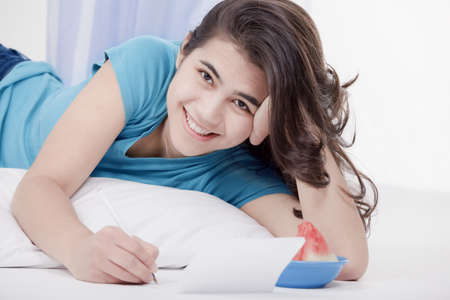 thai teen: Relaxed and happy biracial teen girl or young woman lying on floor pillow writing a letter or note.