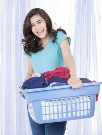 lavanderia: Chica adolescente feliz lavar la ropa, llevaba una carga de ropa en la cesta