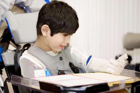 Vijf jaar oude gehandicapte jongen studeren in rolstoel Stockfoto