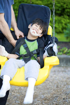 Disabled five year old boy getting strapped  into handicap swing photo