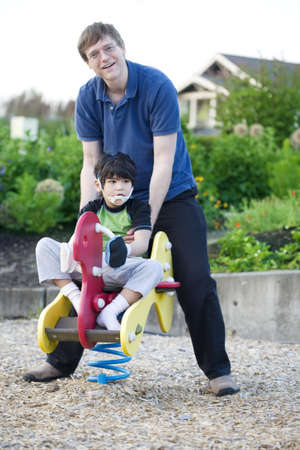 Father helping disabled son play at playground photo