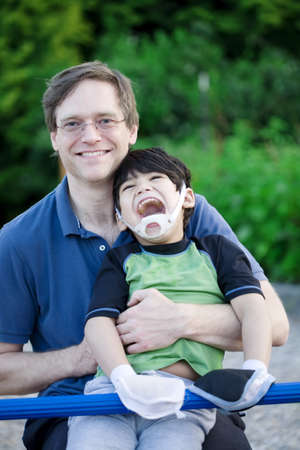 Father holding disabled son at playground photo