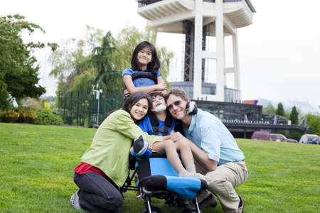 Disabled boy in wheelchair surrounded by family, outdoors by the Space Needle in Seattle Stock Photo - 16057951